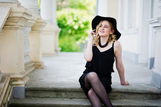 Donna bionda in abito nero, collane e cappello contro la casa d'epoca. Foto Premium
