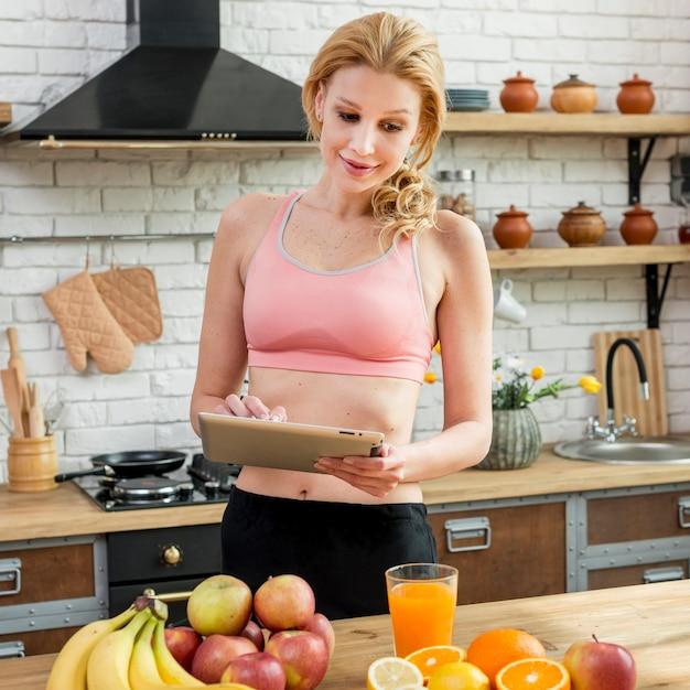 Donna bionda in cucina con frutta Foto Gratuite