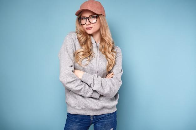 Donna bionda positiva sveglia in un berretto da baseball rosa Foto Premium