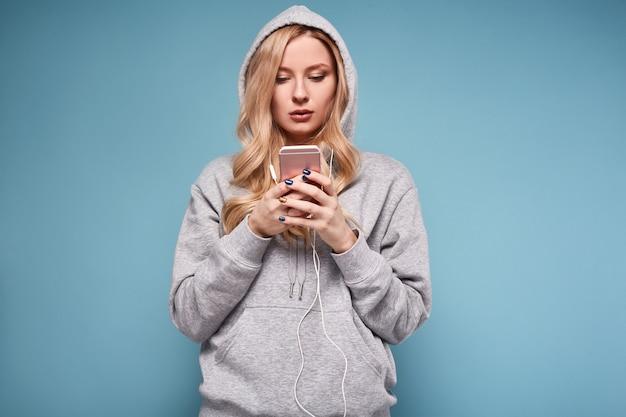 Donna bionda positiva sveglia nella musica d'ascolto di maglia con cappuccio Foto Premium