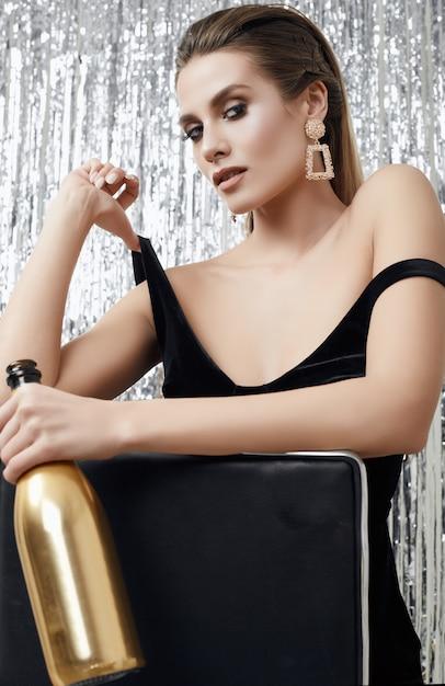 Donna bionda sensuale elegante in vestito nero con una bottiglia di champagne Foto Premium