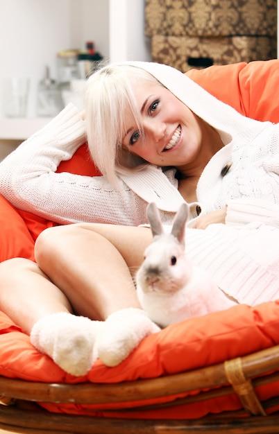 Donna bionda sveglia che si siede sulla sedia con il coniglietto Foto Gratuite