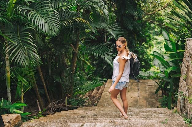 Donna bionda viaggiatore con zaino e sacco a pelo che cammina e che scopre il parco tropicale della giungla, natura di avventura di viaggio in cina, bella destinazione turistica asia, concetto di viaggio di viaggio di vacanze estive di vacanza Foto Premium