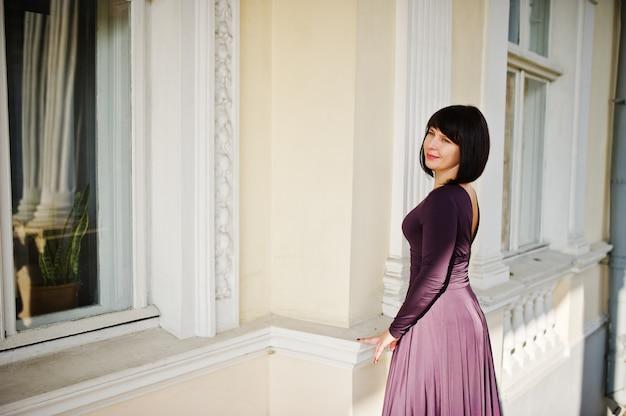 Donna castana adulta alla vecchia casa d'annata del fondo dell'abito viola con le scale. Foto Premium