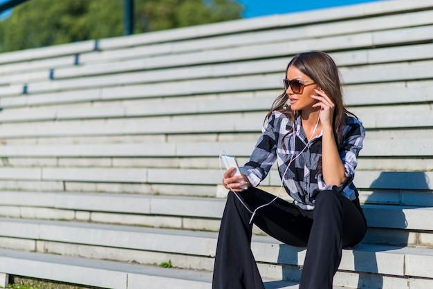 d721147154 Donna castana che si siede sulle scale mentre ascolto musica e usando  smartphone Foto Premium
