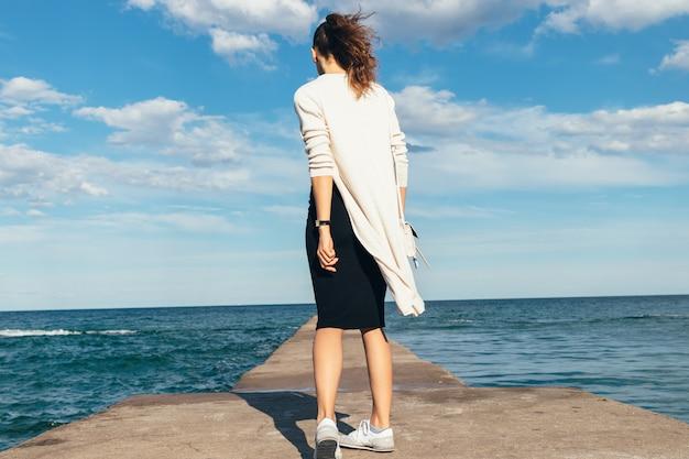 Donna castana esile in una gonna, in un cardigan e nelle scarpe da tennis che cammina sulla spiaggia di estate Foto Premium