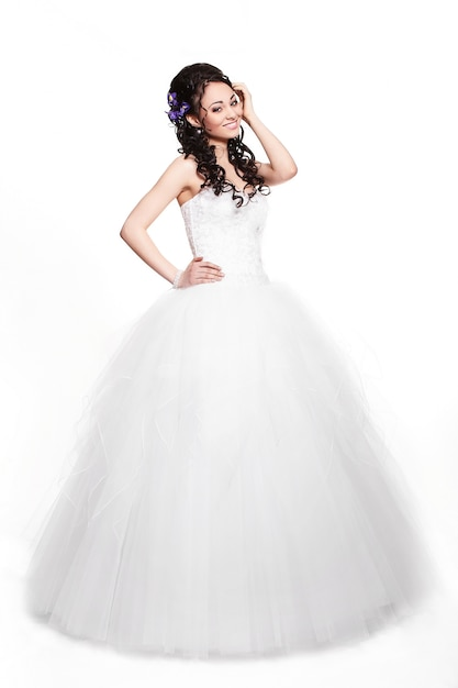 Donna castana felice felice della bella sposa in vestito da sposa bianco con l'acconciatura e trucco luminoso integrale nel retro stile Foto Gratuite