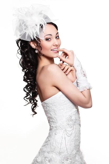 Donna castana felice sexy della bella sposa in vestito da sposa bianco con l'acconciatura e il trucco luminoso Foto Gratuite