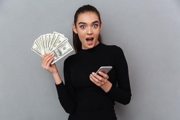 Donna castana felice sorpresa in vestiti neri che tengono soldi Foto Gratuite