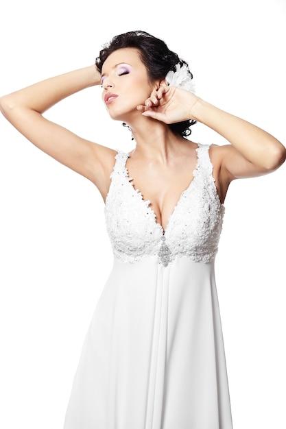 Donna castana sexy felice della bella sposa in vestito da sposa bianco con l'acconciatura e trucco luminoso con il fiore in capelli isolati su bianco Foto Gratuite