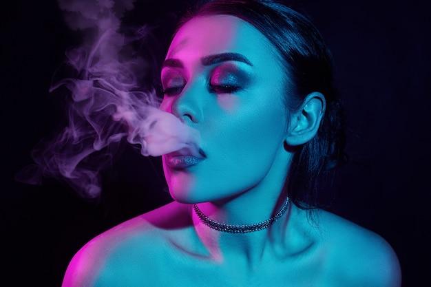 Donna castana splendida seducente di fascino che fuma festa elettronica della sigaretta, retro, annata, estratto, viaggio, vacanze, vacanze, viaggio, turista Foto Premium