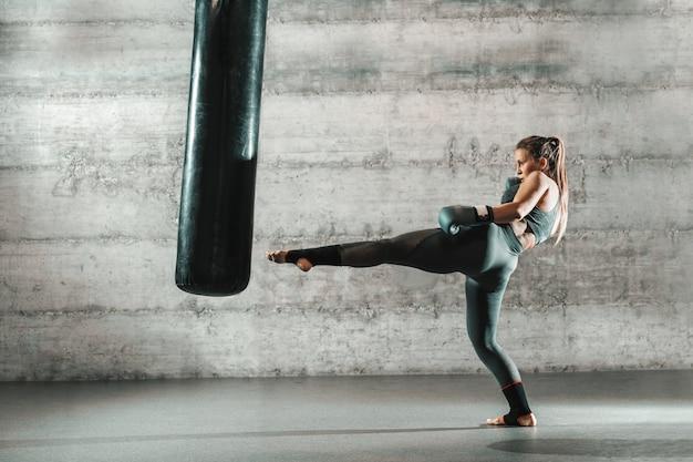 Donna caucasica in abiti sportivi e con guantoni da boxe calciare borsa in palestra. Foto Premium