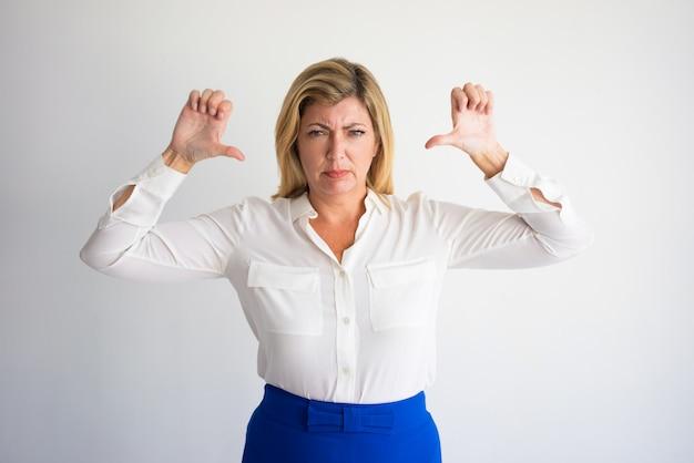 Donna caucasica matura arrabbiata in camicetta formale che mostra i pollici  giù. Foto Premium caf2c2277dd5