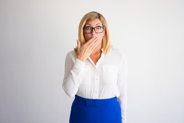 Donna caucasica matura scossa con i vetri che coprono bocca con la mano.  Foto Premium 50e7a48327f3
