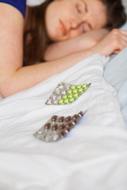 Donna caucasica triste che dorme con le pillole Foto Gratuite