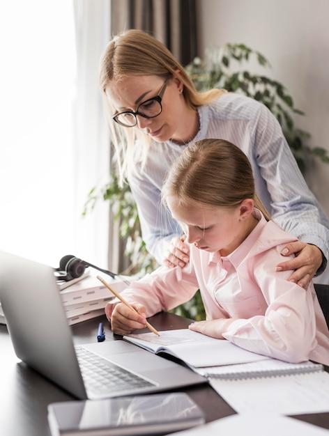 Donna che aiuta una bambina a fare i compiti Foto Gratuite