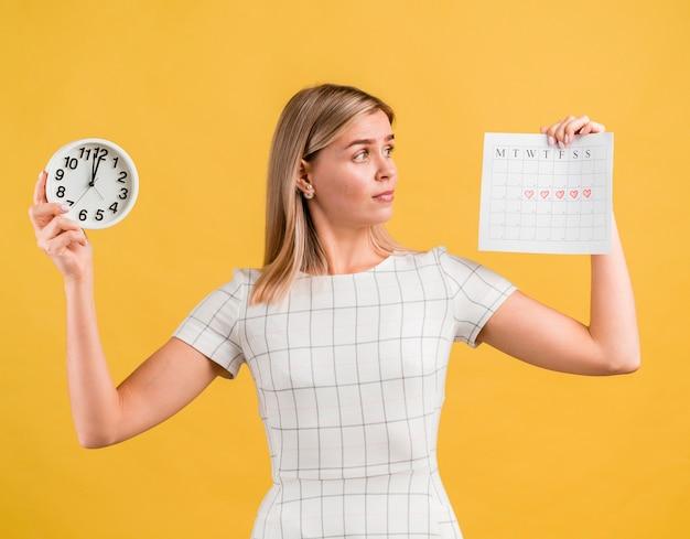 Donna che alza un orologio e un calendario mestruale Foto Gratuite