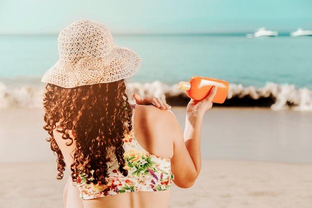 Donna che applica il sunblock sulla spiaggia Foto Gratuite