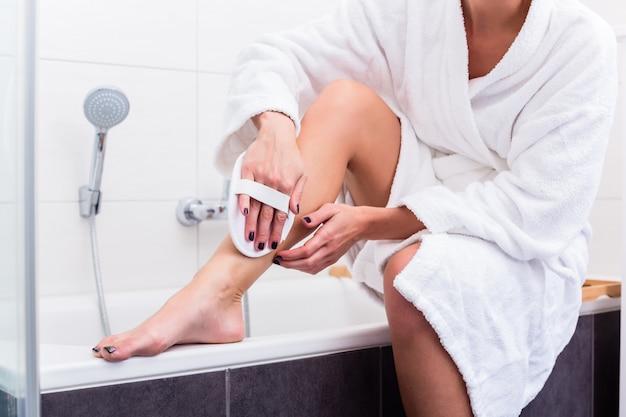 Donna che applica peeling alle gambe Foto Premium