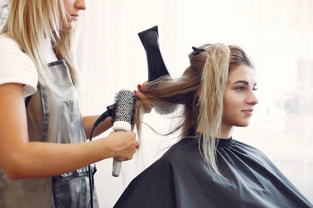 Donna che asciuga capelli in un hairsalon Foto Gratuite