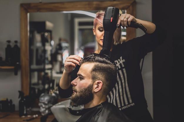 Donna che asciuga i capelli dell'uomo nel negozio di ...
