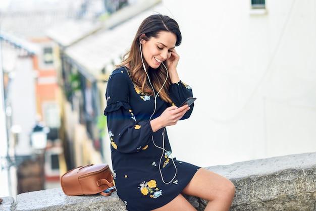 Donna che ascolta la musica con auricolari e smart phone all'aperto. Foto Premium