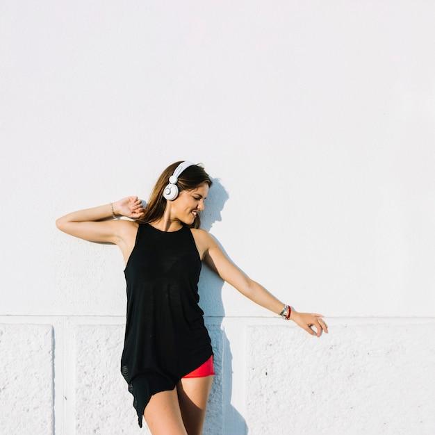 Donna che ascolta la musica in cuffia in piedi davanti al muro Foto Gratuite