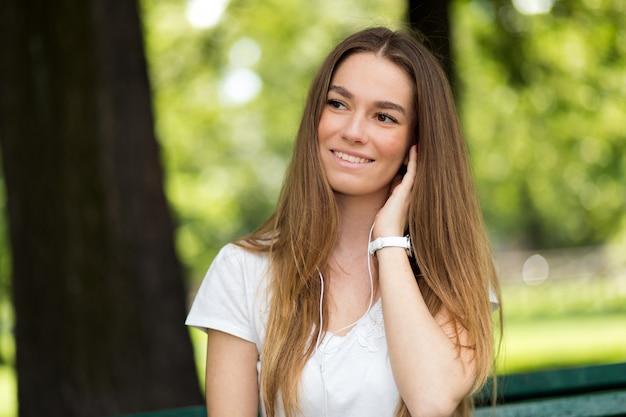 Donna che ascolta la musica seduto su una panchina in un parco in una calda giornata estiva di sole Foto Premium