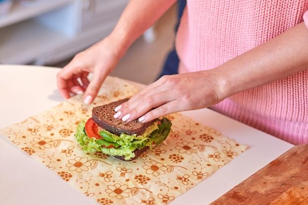 Donna che avvolge un panino sano nell'involucro della cera d'api Foto Premium