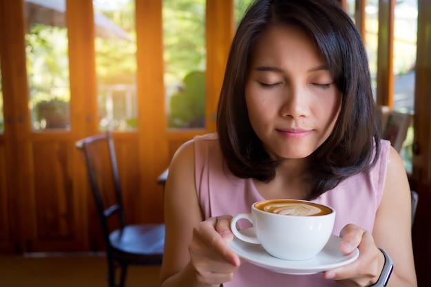 Donna che beve caffè caldo al mattino, rilassarsi tempo Foto Premium