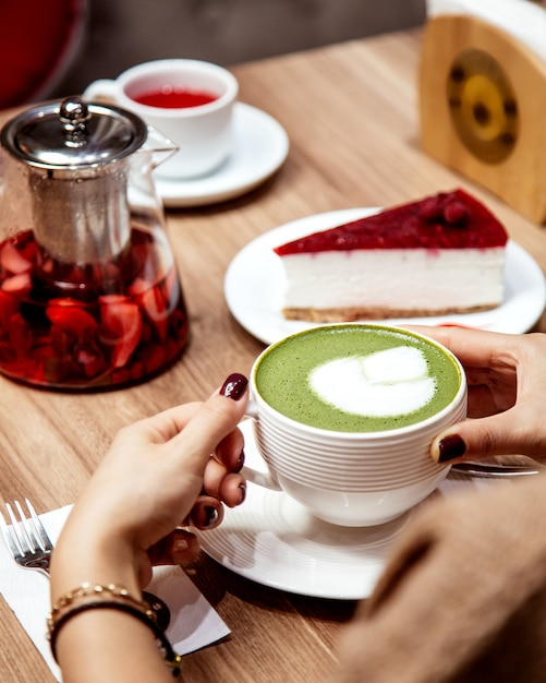 Donna che beve una tazza di tè verde matcha con latte art Foto Gratuite