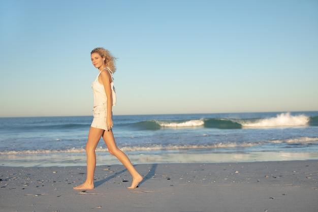 Donna che cammina a piedi nudi sulla spiaggia Foto Gratuite