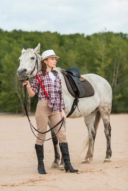 Donna che cammina con un cavallo sulla spiaggia Foto Gratuite