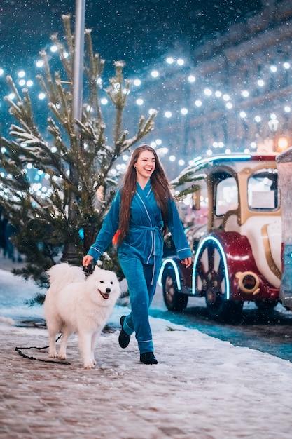 Donna che cammina giù con il cane bianco Foto Gratuite