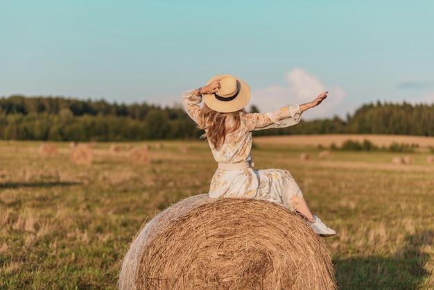 Donna che cammina nel campo con covoni di fieno Foto Premium