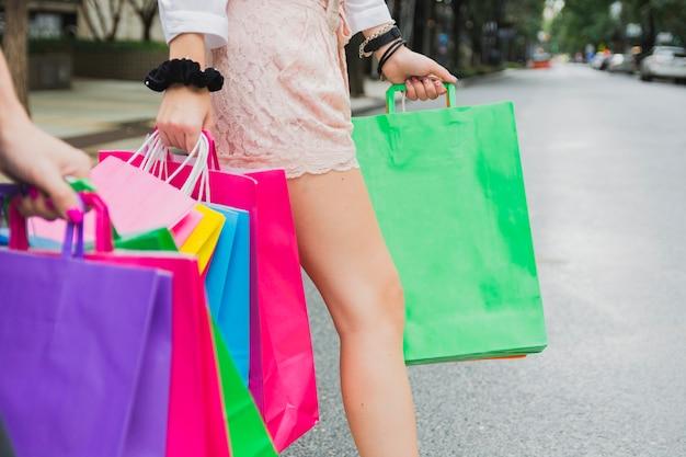 Donna che cammina sulla strada con borse della spesa Foto Gratuite