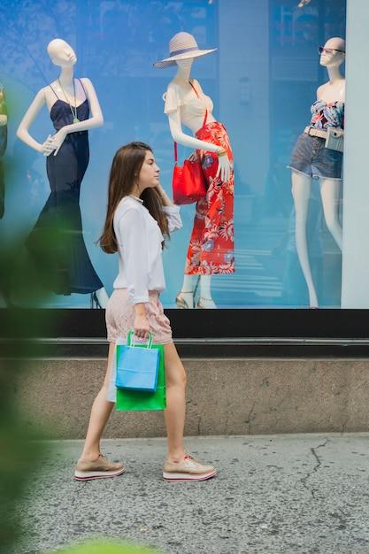 Donna che cammina vicino alla finestra del negozio Foto Gratuite