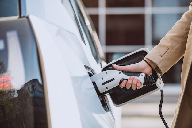 Donna che carica l'auto elettrica alla stazione di gas elettrica Foto Gratuite