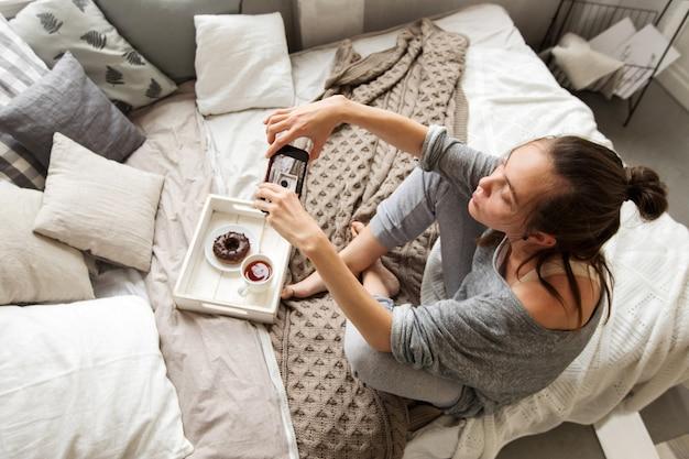 Donna che cattura il colpo del vassoio con cibo sul letto Foto Premium