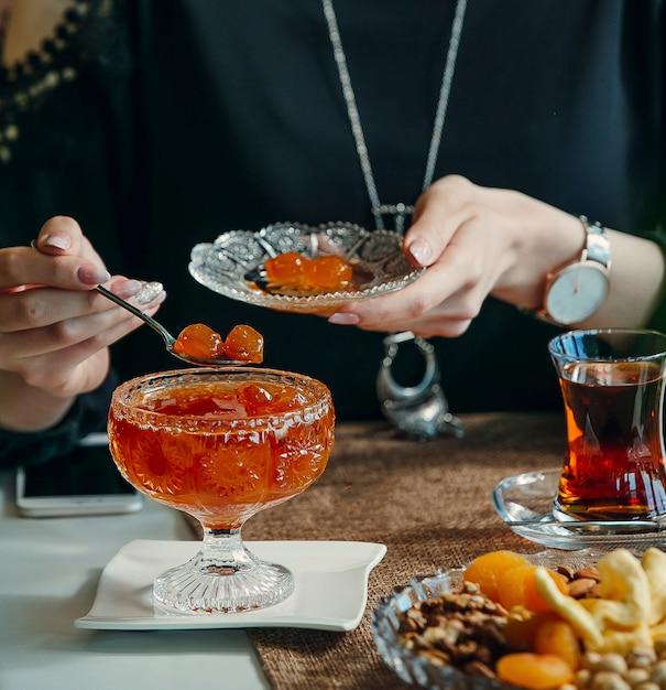 Donna che cattura la marmellata di amarene dalla ciotola di cristallo, bevendo tè nero Foto Gratuite