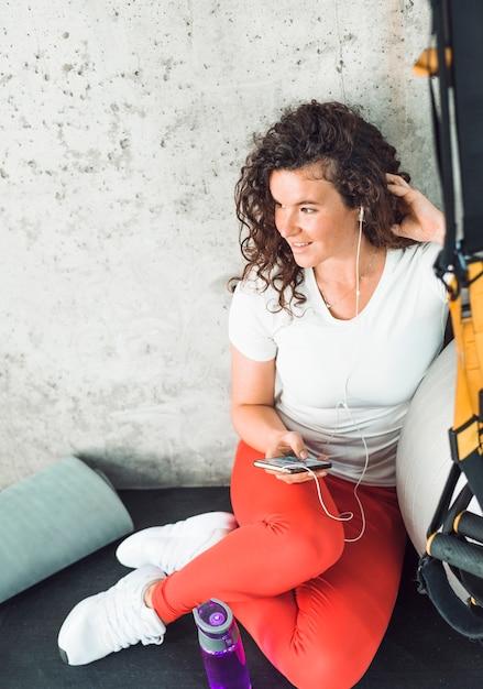 Donna che cattura rottura dopo allenamento e ascoltare musica sul cellulare in palestra Foto Gratuite