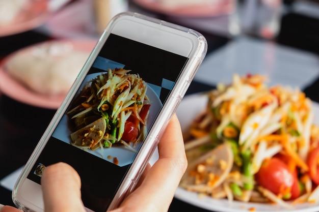 Donna che cattura una foto dell'insalata verde tailandese della papaia con lo smartphone Foto Premium