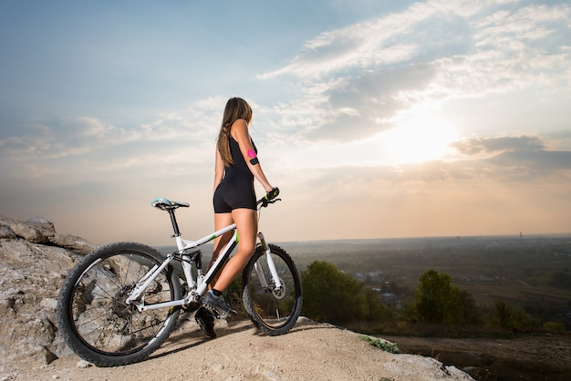 Donna che cavalca sulla bicicletta sportiva sulla collina di montagna Foto Premium