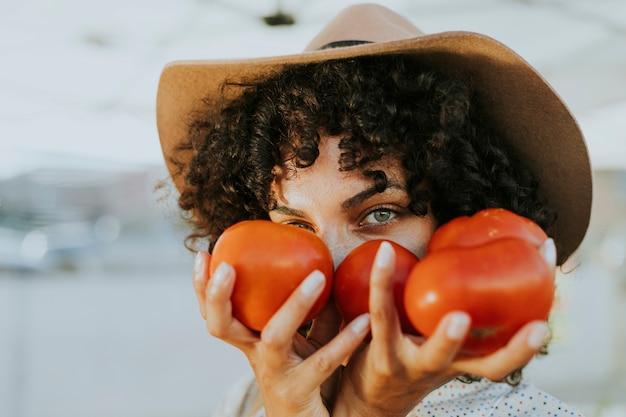 Donna che compra i pomodori in un mercato degli agricoltori Foto Gratuite