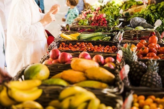 Donna che compra verdura e frutta al mercato degli agricoltori Foto Gratuite