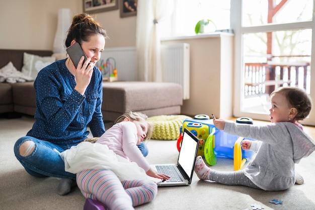 Donna che comunica sul cellulare mentre sua figlia guardando lo schermo del laptop Foto Gratuite