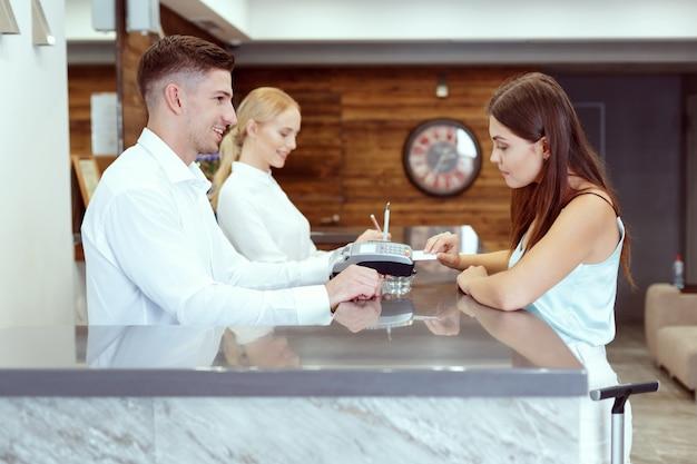 Donna che controlla alla reception dell'hotel Foto Premium