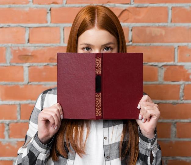 Donna che copre il viso con il libro Foto Gratuite