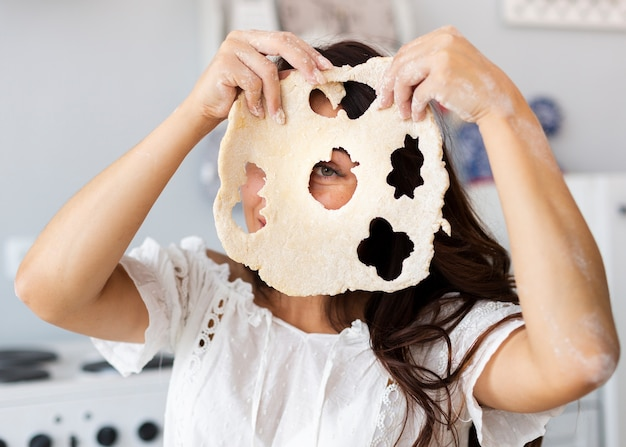 Donna che copre il viso con pasta di biscotti Foto Gratuite