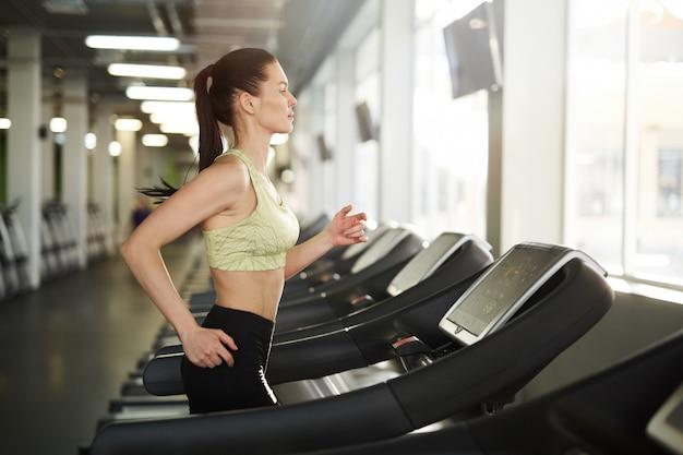 Donna che corre sul tapis roulant in palestra Foto Premium
